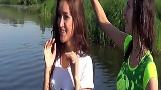 Cute schoolgirls playing in river