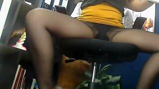 Under the office desk. Long legs in black pantyhose